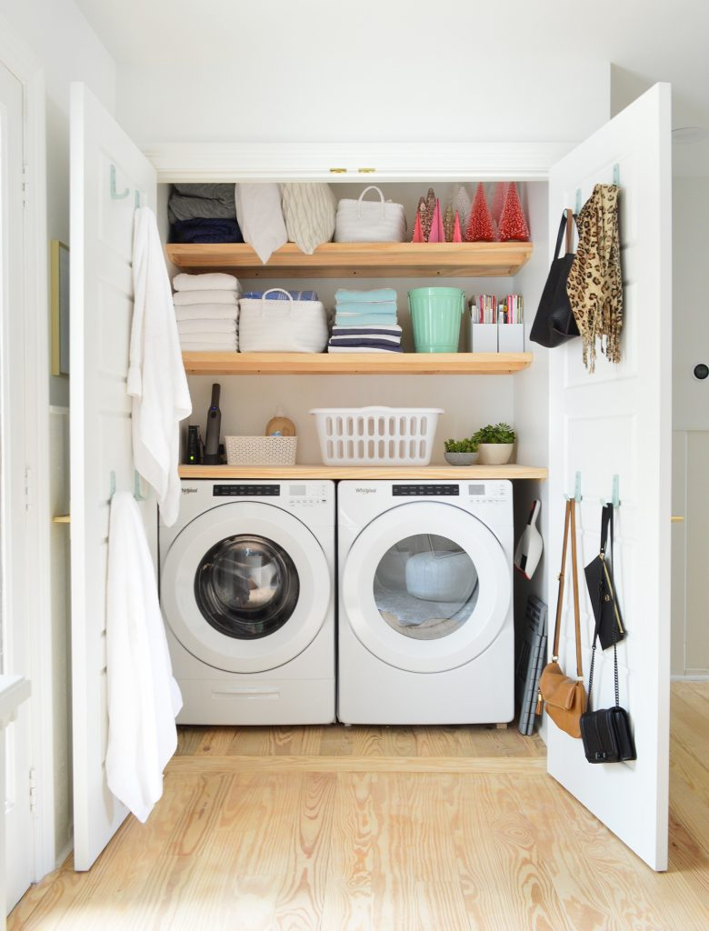 Laundry room closet open showing wood shelving