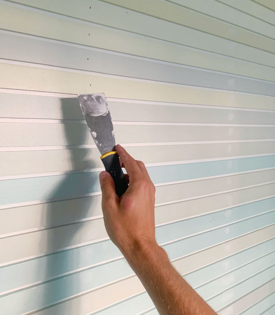 Hand Spackling Nail Holes On Striped Wall Treatment