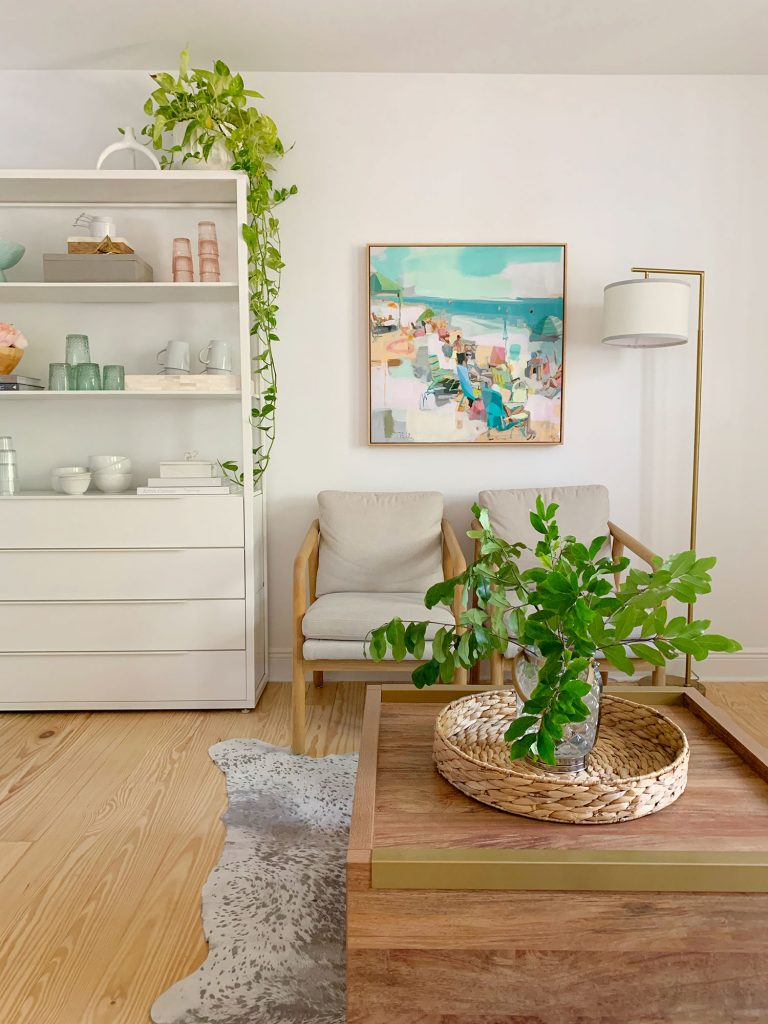 Side view of sitting area with plants on coffee table and hanging from kitchen shelf