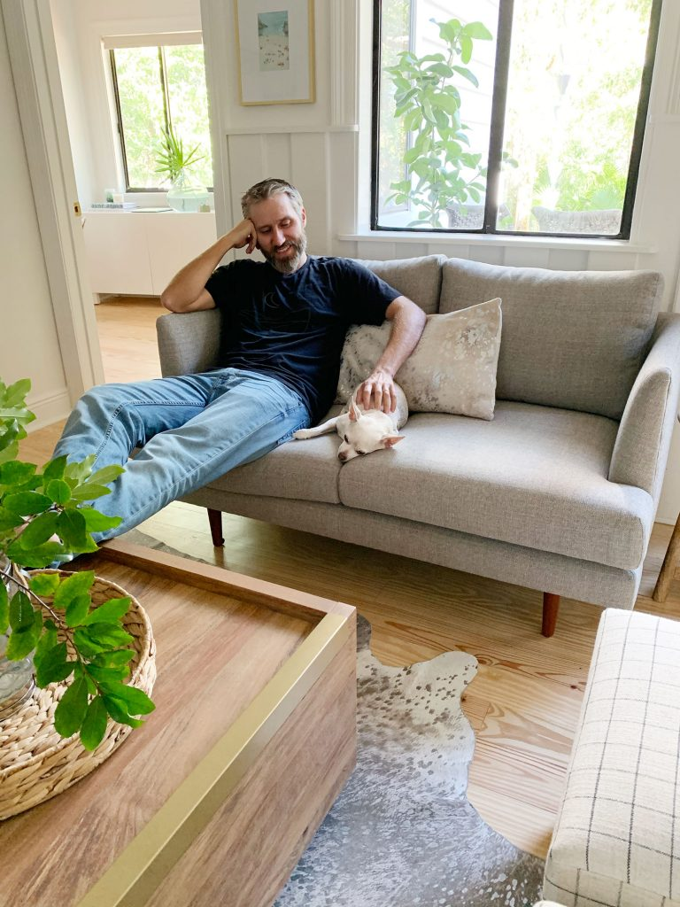John sitting on gray loveseat with chihuahua next to him