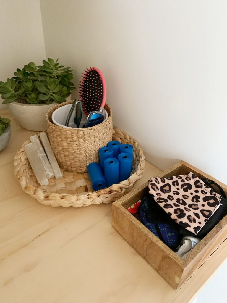 Baskets and bins on laundry shelf holding entryway accessories like masks dog bags and sunglasses