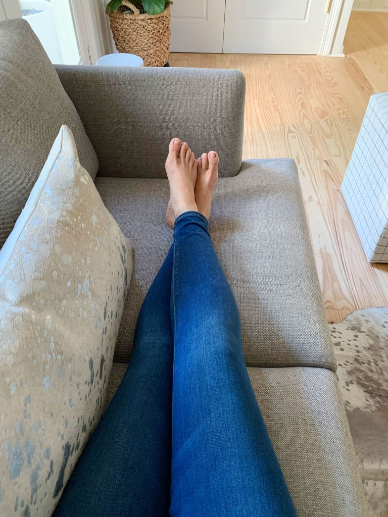 Sherry's legs stretched out on gray loveseat