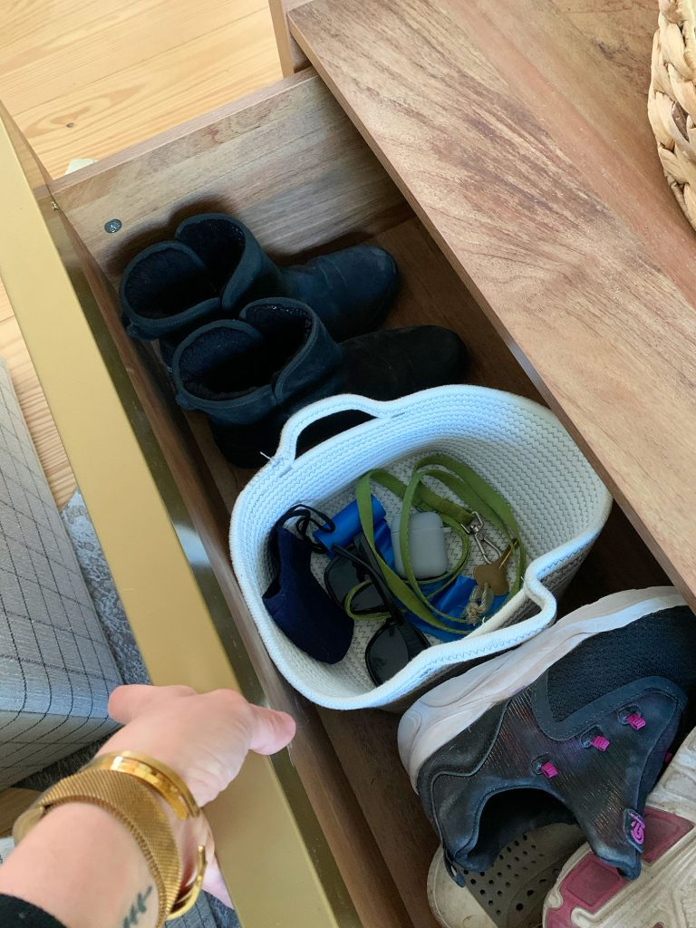 Open drawer of wood storage coffee table showing shoes and basket with keys